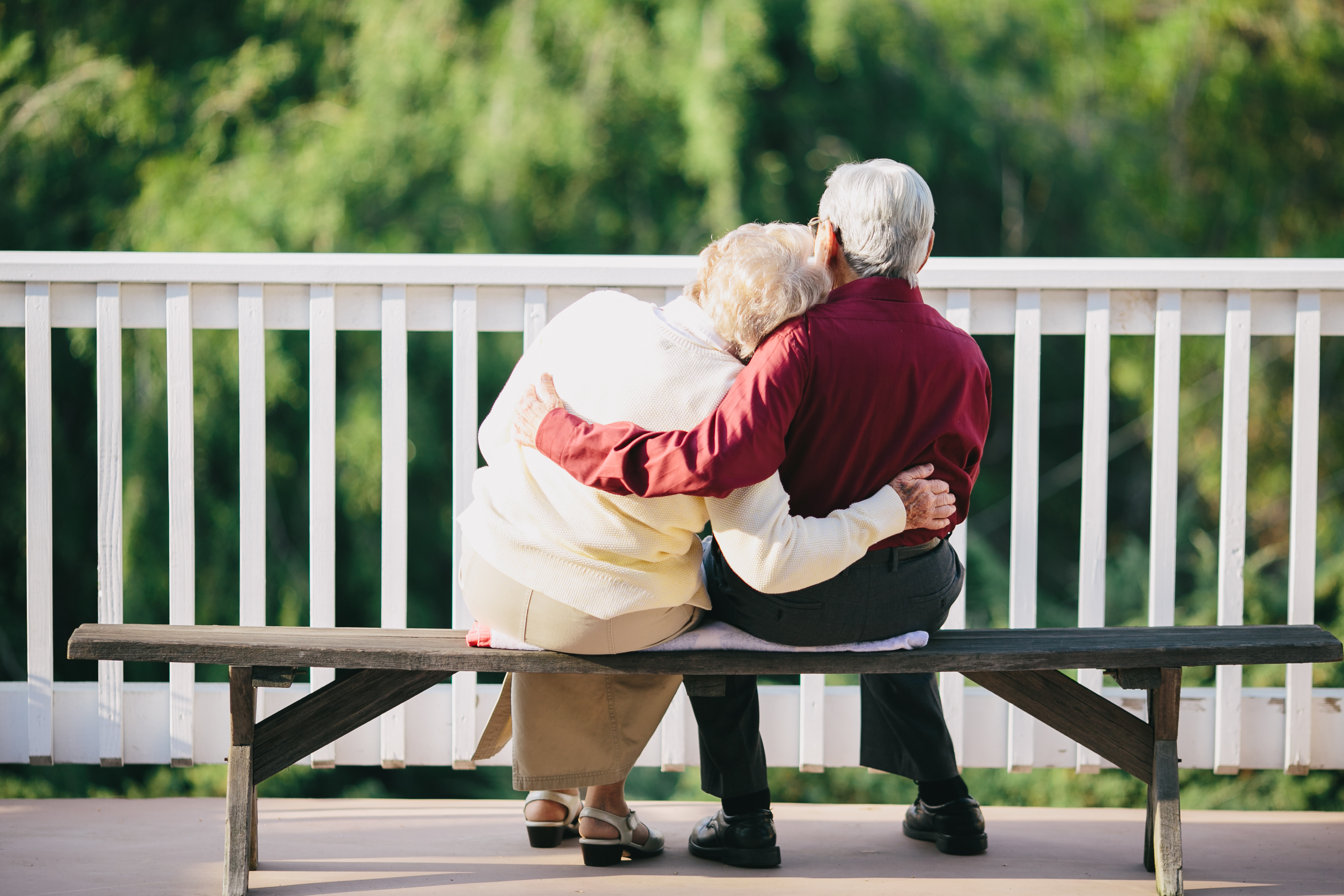 two elderly people hugging on a bench