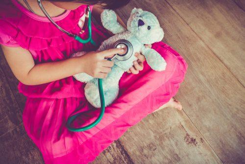 Girl using stethoscope on teddy bear