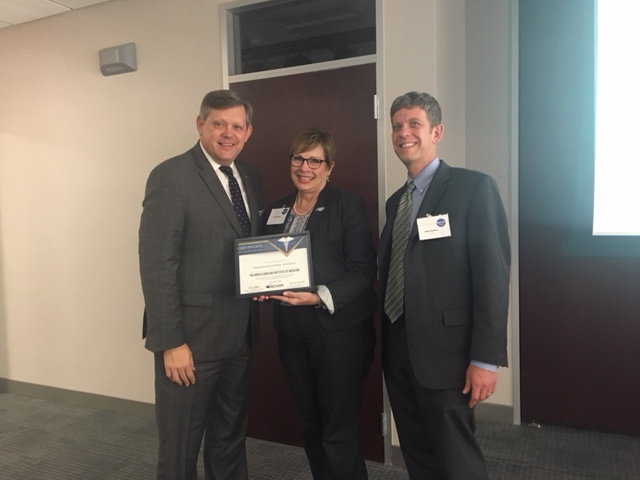 NCIOM CEO Adam Zolotor (right) poses with one of the Fellows, Sen. Mike Woodard (left) and NCIOM Board Chair Kim Schwartz.