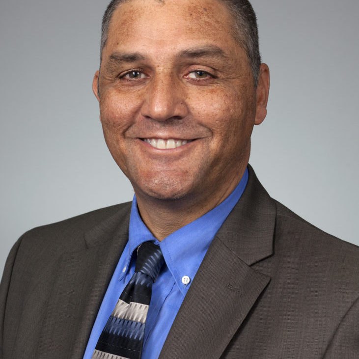 headshot of Ronny A. Bell, PhD, wearing a dark jacket, blue shirt, and striped tie