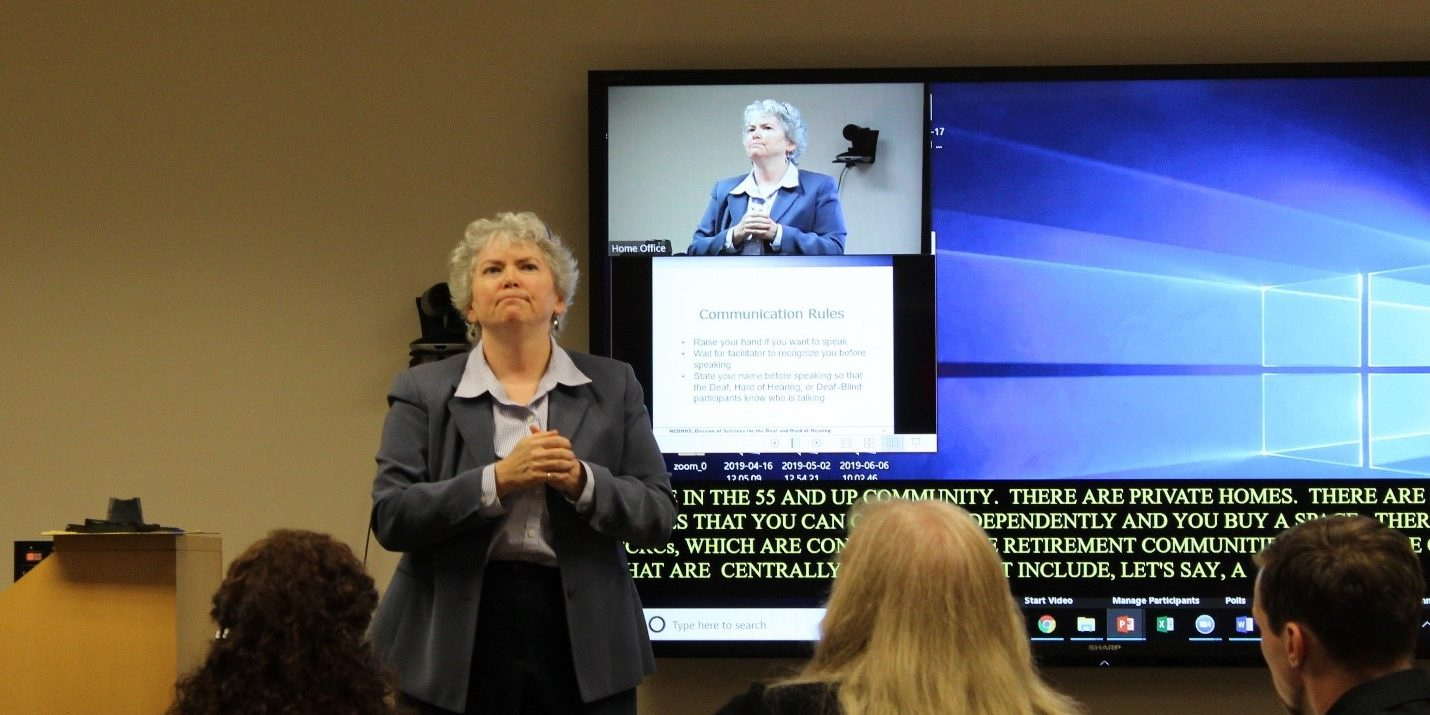 Jane Withers, director of the Division of Services for the Deaf and Hard of Hearing from NCDHHS signing her presentation at the task force meeting