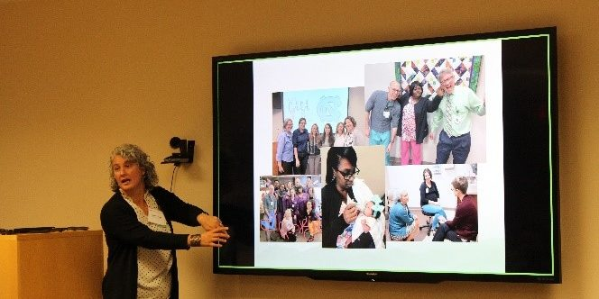 Melinda Ramage, a white woman with grey hair in a black cardigan, gestures toward a screen of photos in a conference room