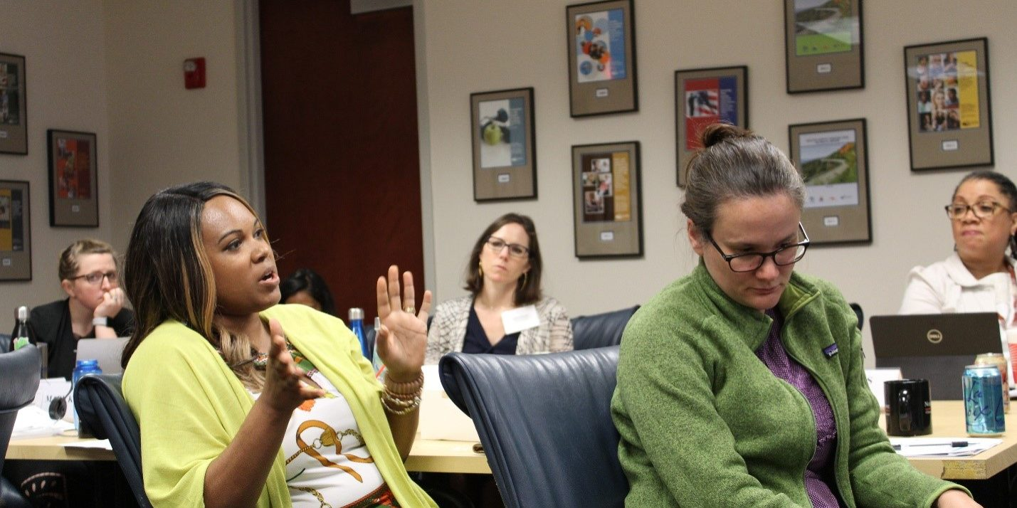 A black woman in chartreuse speaks expressively as a white woman in a green sweater listens intently next to her and several people look on from the background